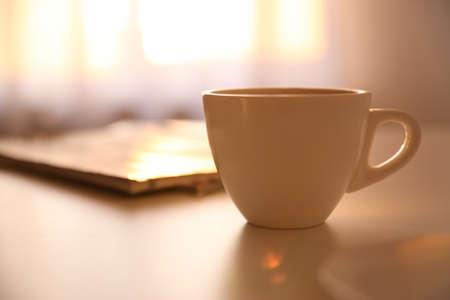 Taza de bebida caliente en la mesa, espacio para texto. Mañana perezosa Foto de archivo