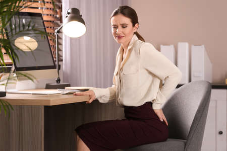 Young woman suffering from hemorrhoid at workplace in office