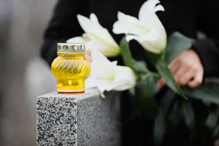 Woman holding white lilies near grey granite tombstone outdoors, focus on candle. Funeral ceremony 스톡 콘텐츠