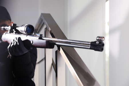 Hired professional killer with sniper rifle indoors, closeup