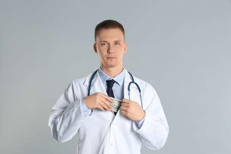 Doctor putting bribe into pocket on grey background. Corruption in medicine Stockfoto