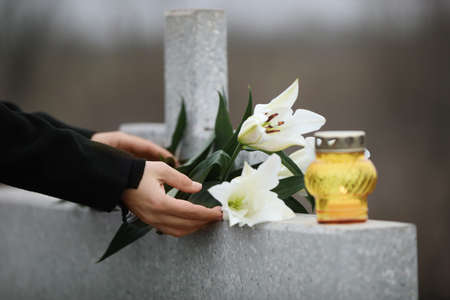 Woman holding white lilies near light grey granite tombstone with candle outdoors, closeup. Funeral ceremony