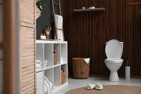 Elegant modern bathroom with toilet bowl near wooden wall