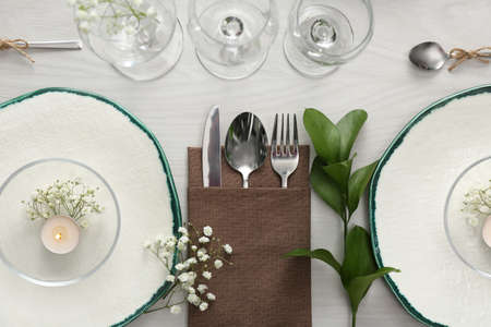 Elegant table setting with green plants on white wooden background, flat lay Reklamní fotografie
