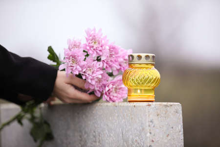 Woman holding chrysanthemum flowers near grey granite tombstone with candle outdoors, closeup. Funeral ceremony