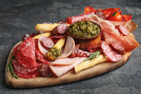 Tasty ham and other delicacies served on grey table, closeup