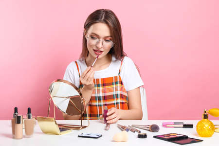 Beauty blogger applying lipgloss at table on pink background