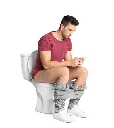 Man with smartphone sitting on toilet bowl, white background Standard-Bild