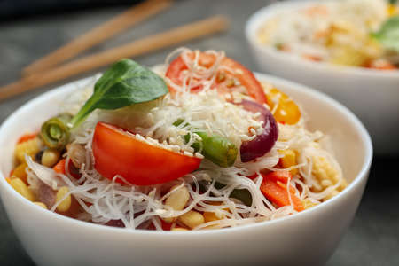 Tasty cooked rice noodles with vegetables on table, closeup