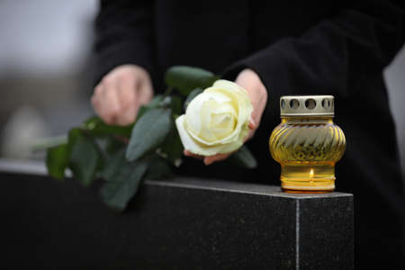 Woman holding white rose near black granite tombstone with candle outdoors, closeup. Funeral ceremony 스톡 콘텐츠
