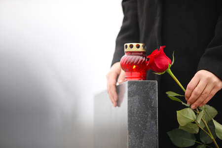Woman holding red rose near black granite tombstone with candle outdoors, closeup. Funeral ceremony