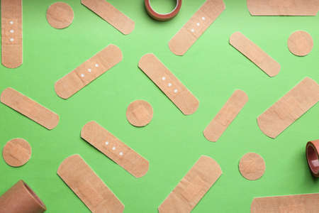 Different types of sticking plasters on green background, flat lay