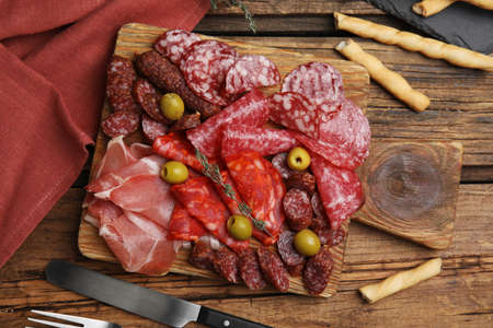 Tasty prosciutto with other delicacies served on wooden table, flat lay Фото со стока