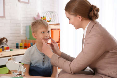 Speech therapist working with little boy in office