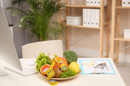 Nutritionist's workplace with fruits, vegetables, measuring tape and body fat calipers on table