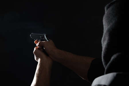 Professional killer with gun on black background, closeup