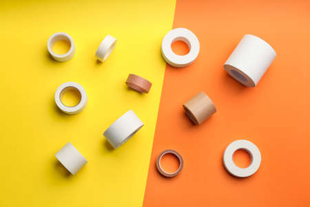 Sticking plaster rolls on color background, flat lay Imagens