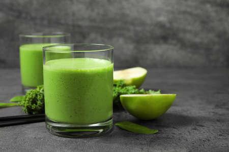 Leckerer frischer Grünkohl-Smoothie auf grauem Tisch