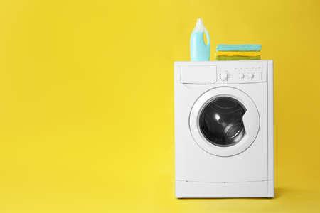 Nowoczesna pralka ze stosem ręczników i detergentu na żółtym tle, miejsca na tekst. Dzień prania Zdjęcie Seryjne