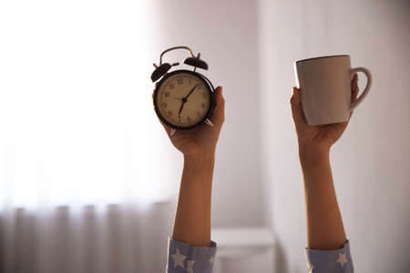 Woman with cup and alarm clock at home, closeup. Morning time