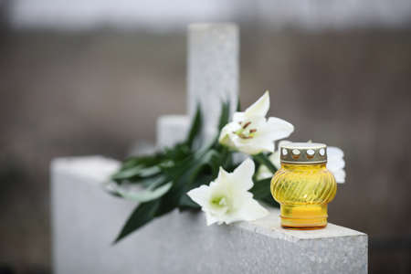 White lilies and candle on light grey granite tombstone outdoors. Funeral ceremony 스톡 콘텐츠