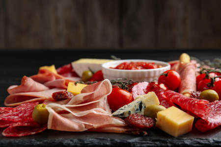Tasty prosciutto with other delicacies served on table, closeup