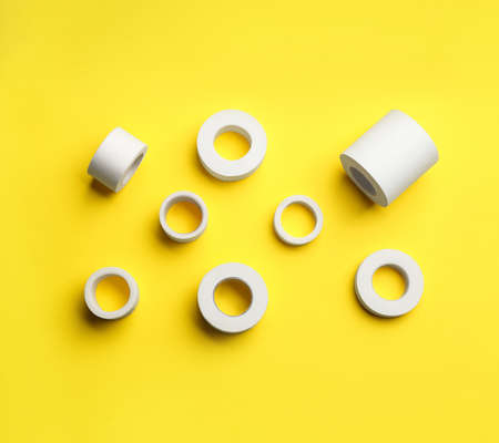 Sticking plaster rolls on yellow background, flat lay