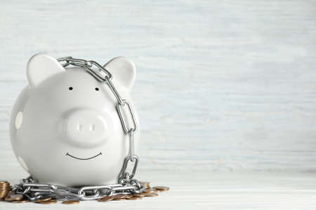 Piggy bank with steel chain and coins on white wooden table, space for text. Money safety concept Stock fotó
