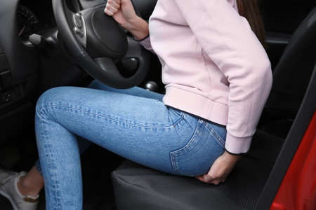 Frau mit Hämorrhoidenschmerzen im Auto, Nahaufnahme Standard-Bild