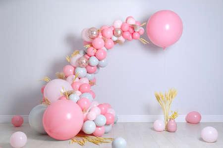 Bella composizione con palloncini e spighette vicino al muro chiaro Archivio Fotografico