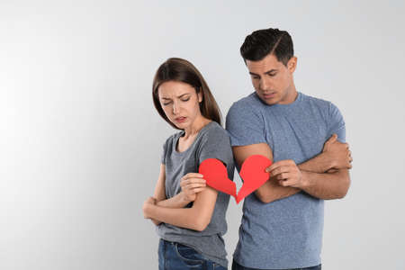 Couple with torn paper heart on light background. Relationship problems