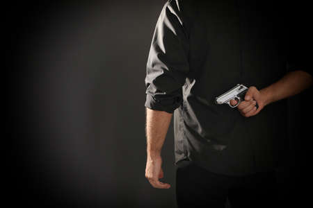 Professional killer with gun on black background, closeup. Space for text