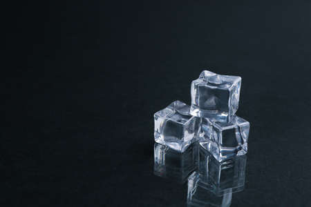 Crystal clear ice cubes on black background. Space for text 免版税图像
