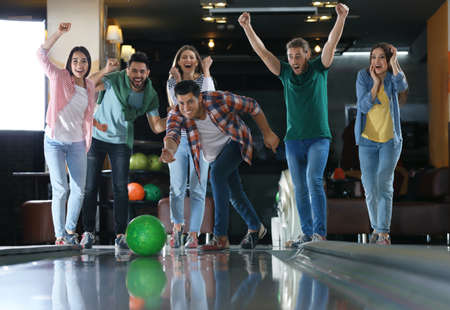 Man throwing ball and spending time with friends in bowling club
