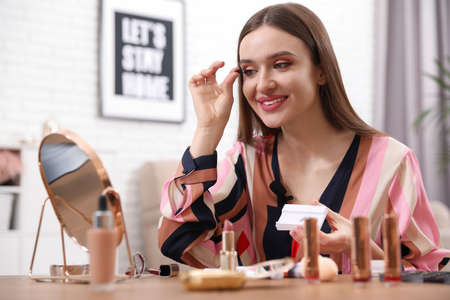 Beauty blogger applying false lashes at home
