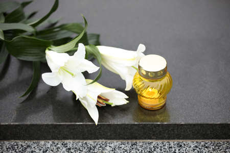 White lilies and candle on black granite tombstone. Funeral ceremony