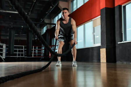 Man working out with battle ropes in modern gym