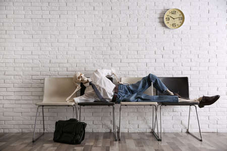 Human skeleton in office wear lying on chairs near brick wall indoors