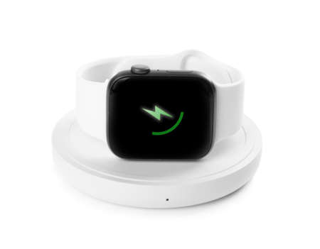 Smartwatch charging with wireless pad isolated on white