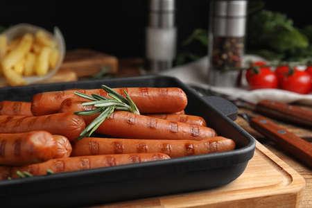 Délicieuses saucisses grillées au romarin sur table en bois, gros plan Banque d'images