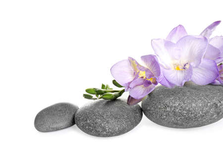 Spa stones and freesia flowers on white background