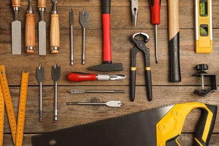 Flache Laienzusammensetzung mit Tischlerwerkzeugen auf Holzuntergrund