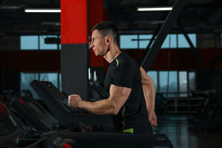 Man working out on treadmill in modern gym