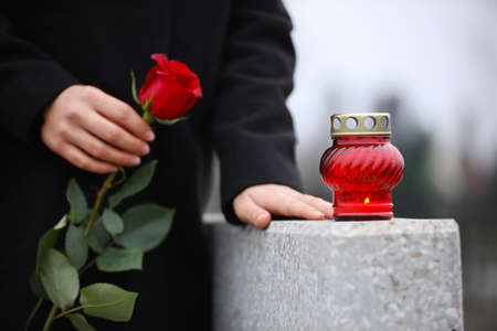 Woman holding red rose near grey granite tombstone with candle outdoors, closeup. Funeral ceremony 스톡 콘텐츠