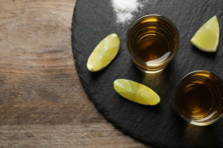 Mexican Tequila shots, lime slices and salt on wooden table, top view 免版税图像