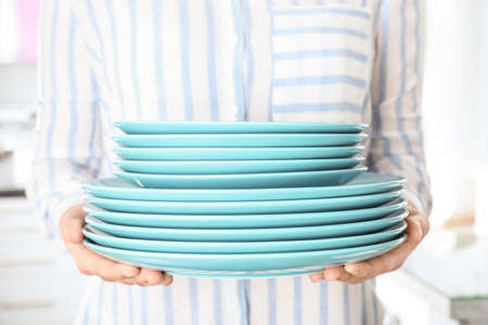Woman holding stack of clean blue plates in kitchen, closeup