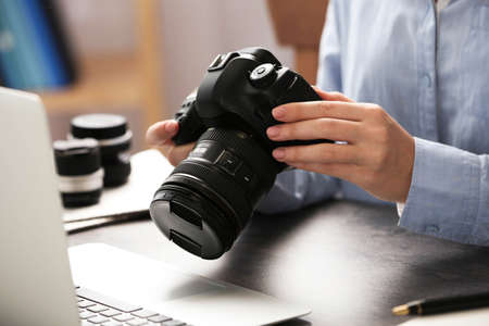 Journalist with camera working at table, closeup