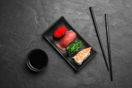Set of delicious sushi on grey table, flat lay