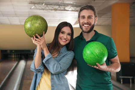 Happy young couple with balls in bowling club