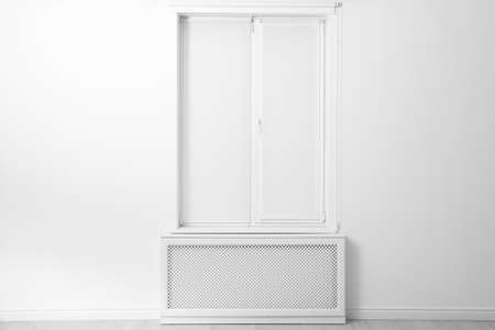 Modern window with closed Roman blinds in empty room Stock fotó